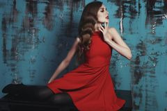 Bella donna in vestito rosso con capelli ricci Fotografia Stock Libera da Diritti