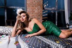 Bella donna in vestito rosso elegante che si trova sul sofà moderno fotografie stock