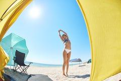 Bella donna vicino alla tenda vista dall'interno della tenda sulla spiaggia sabbiosa e del mare un giorno soleggiato luminoso Fotografia Stock
