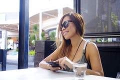 Bella e donna asiatica felice che per mezzo del telefono cellulare che manda un sms sopra dentro Fotografia Stock Libera da Diritti