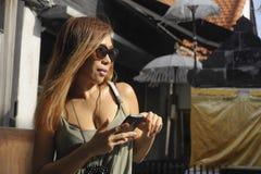 Bella e donna asiatica felice che per mezzo del telefono cellulare che manda un sms sul sorridere sociale di media di Internet ri Immagini Stock