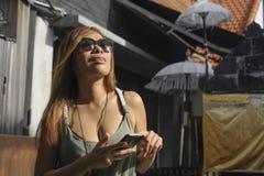 Bella e donna asiatica felice che per mezzo del telefono cellulare che manda un sms sul sorridere sociale di media di Internet ri Immagini Stock Libere da Diritti