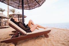 Bella e donna castana sexy in bikini che si rilassa sulla spiaggia dell'oceano sotto la palma Viaggiando, festa, concetto di vaca Fotografie Stock