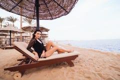Bella e donna castana sexy in bikini che si rilassa sulla spiaggia dell'oceano sotto la palma Viaggiando, festa, concetto di vaca Immagine Stock Libera da Diritti