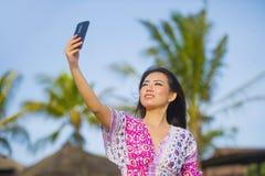 Bella e donna cinese asiatica splendida felice in vestito da fascino che prende la foto del selfie dell'autoritratto con il telef Immagine Stock Libera da Diritti