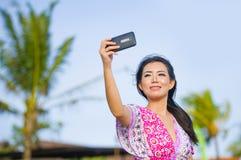 Bella e donna cinese asiatica splendida felice in vestito da fascino che prende la foto del selfie dell'autoritratto con il telef Fotografia Stock Libera da Diritti