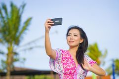 Bella e donna cinese asiatica splendida felice in vestito da fascino che prende la foto del selfie dell'autoritratto con il telef Fotografia Stock