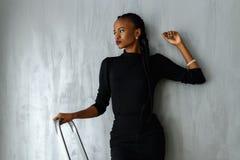 Bella e donna di colore sexy in vestito scuro che posa distogliendo lo sguardo mano pendente sulla parete grigia allo studio Fotografia Stock