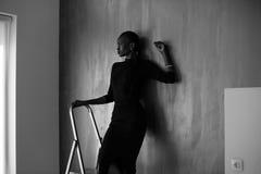 Bella e donna di colore sexy in vestito scuro che posa distogliendo lo sguardo mano pendente sulla parete grigia allo studio Immagine Stock