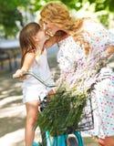 Bella e giovane donna felice sulla bicicletta con sua figlia Immagine Stock Libera da Diritti