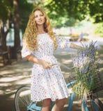 Bella e giovane donna felice sulla bicicletta nel parco di estate Fotografia Stock