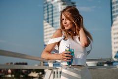 Bella e ragazza allegra con un cocktail fotografia stock libera da diritti