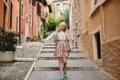 Bella e ragazza di modello bionda sveglia in gonna rosa, in blusa bianca ed in bomber che regola i suoi capelli e che cammina giù fotografia stock libera da diritti