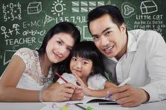 Bella famiglia che fa compito scolastico Fotografia Stock Libera da Diritti