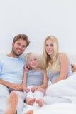 Bella famiglia che si siede nel letto Fotografia Stock