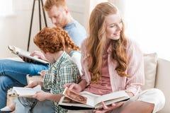 Bella famiglia della testarossa che si siede insieme sul sofà e sui libri di lettura Immagini Stock