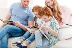 Bella famiglia della testarossa che si siede insieme sul sofà e sui libri di lettura Fotografia Stock