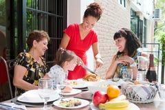 Bella famiglia ispanica che gode insieme di un pasto domestico all'aperto fotografia stock