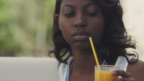 Bella femmina afroamericana in abbigliamento casual che gode del tempo libero che si siede alla tavola in caffè facendo uso del c video d archivio
