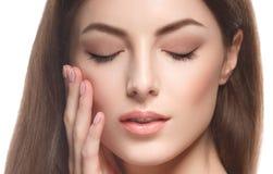 Bella fine del fronte del ritratto della donna su che tocca il suo fronte dalle dita isolate su bianco Fotografia Stock Libera da Diritti