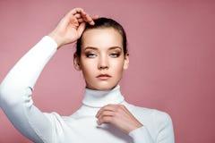Bella fine del fronte della donna sullo studio sul rosa fotografia stock libera da diritti