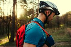 Bella fine sul colpo di giovane ciclista barbuto bello dell'uomo che indossa casco protettivo, maglietta blu e zaino rosso, guard fotografia stock libera da diritti