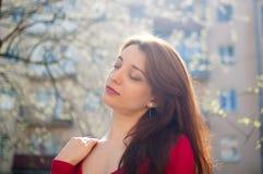 Bella fine sul ritratto di giovane donna castana con i capelli di salto del vento sul fondo urbano delle costruzioni immagini stock