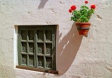 Bella finestra di legno scolpita e una piantatrice di terracotta con i fiori rossi che appendono sulla parete esterna bianca, Are immagini stock