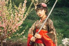 Bella geisha in kimono con la spada del samurai fotografia stock libera da diritti
