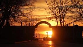 Bella gente del mare con il tramonto La spiaggia nebbiosa del tramonto delle scogliere delle rocce della costa ondeggia schiaccia stock footage