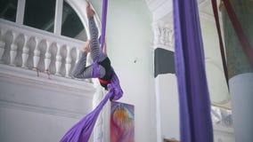Bella ginnasta dell'aria della donna che si esercita sulla seta aerea in uno studio stock footage