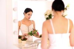 Bella giovane ballerina che sta contro lo specchio immagine stock