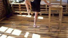 Bella giovane ballerina nei movimenti di pratica di ballo del tutu nero alla sala da ballo Ragazza esile incantante in vestito ne video d archivio