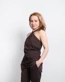 Bella giovane bionda con le gambe lunghe in un agrostide minuto con le spalle nude e la posa dei pantaloni Fotografie Stock Libere da Diritti
