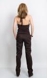 Bella giovane bionda con le gambe lunghe in un agrostide minuto con le spalle nude e la posa dei pantaloni Vista posteriore Fotografie Stock