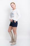 Bella giovane bionda in una blusa bianca, negli shorts blu ed in un'alta posa degli stivali Immagine Stock
