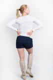 Bella giovane bionda in una blusa bianca, negli shorts blu ed in un'alta posa degli stivali Fotografia Stock