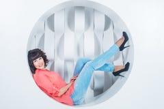 Bella giovane bugia sicura della donna nel cerchio sulla parete di bianco del fondo Fotografia Stock Libera da Diritti