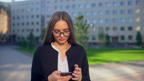 Bella giovane camicia bianca d'uso dello studente o della donna di affari ed utilizzare Smart Phone moderno nella città, professi stock footage