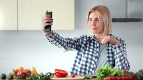 Bella giovane casalinga che prende selfie facendo uso dello smartphone alla cucina durante la cottura dell'alimento sano video d archivio