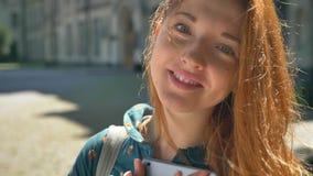 Bella giovane compressa della tenuta della donna dello zenzero ed esaminare macchina fotografica, stante sulla via durante il gio video d archivio