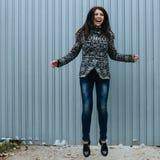 Bella giovane donna in abbigliamento casual che salta contro il recinto fotografia stock