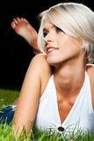 Bella giovane donna abbronzata che si trova sull'erba immagini stock libere da diritti