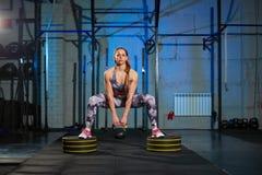 Bella giovane donna in abiti sportivi grigi che fanno esercizio con peso Misura dell'incrocio Fotografia Stock Libera da Diritti
