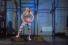Bella giovane donna in abiti sportivi grigi che fanno esercizio con peso Misura dell'incrocio immagini stock