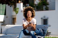 Bella giovane donna africana che si siede all'aperto sul banco con il telefono cellulare Immagini Stock