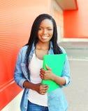 Bella giovane donna africana sorridente del ritratto con la cartella Fotografia Stock