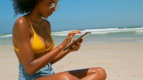 Bella giovane donna afroamericana che utilizza compressa digitale sulla spiaggia nel sole archivi video