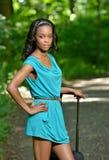 Bella giovane donna afroamericana con la valigia sulla strada Fotografie Stock