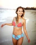 Bella giovane donna al tramonto sulla spiaggia Fotografia Stock